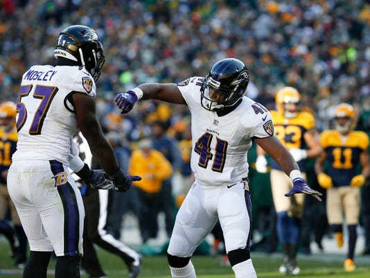 Baltimore Ravens' C.J. Mosley and Anthony Levine react after a stop during the second half of an NFL football game against the Green Bay Packers Sunday, Nov. 19, 2017, in Green Bay, Wis. (AP Photo/Mike Roemer)