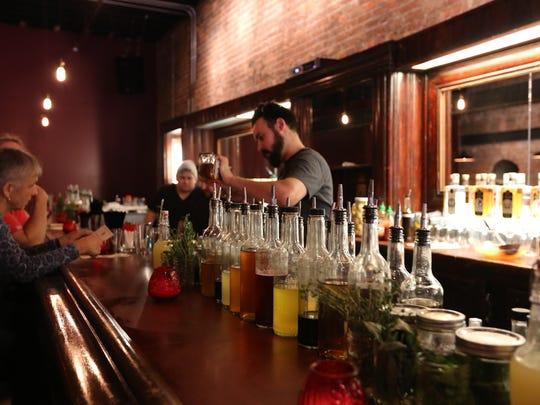 Bartender Evan Dawber at Detroit City Distillery in Detroit pours a drink.