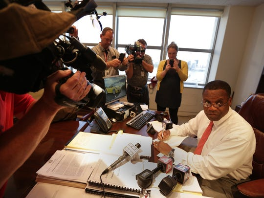 In front of the news media, Detroit emergency financial manager Kevyn Orr signs an order Thursday, Sept. 28, 2014, that  transfers all authority back to Mayor Mike Duggan and the City Council. Orr had control of city decision-making for 18 months. He will continue to handle the city's bankruptcy matters.