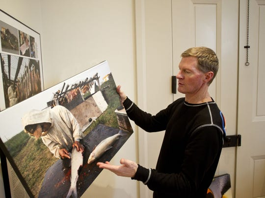 Oceanic explorer and Iowa native David Thoreson holds one of his photographs Jan. 21 while discussing his new exhibit at the Gallery for Arts, Humanities, & Sciences at the Old Capitol Museum in Iowa City.