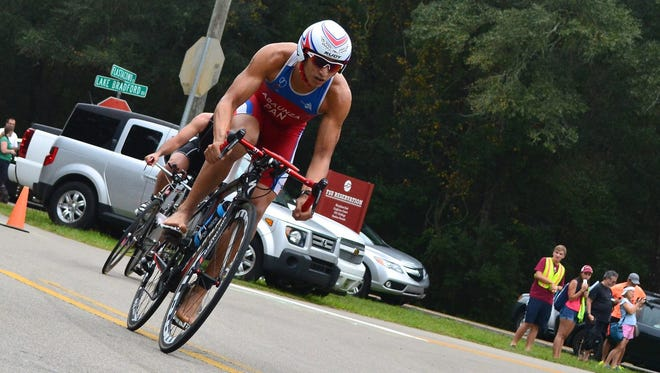 Armando Abaunza cycles past competitors on the bike course during last year's Tri the Rez triathlon.