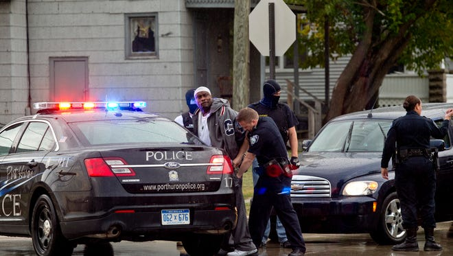 Members of the Port Huron Police Department and St. Clair County Drug Task Force detain a man as part of a drug investigation Tuesday, October 20, 2015 at 10th Avenue and Stanton Street in Port Huron.