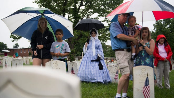 Sue Wright, center, who is dressed as Mary Lincoln, tries to keep dry during a Memorial Day ceremony at Knoxville National Cemetery on Monday, May 28, 2018.