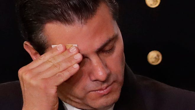 """Mexican President Enrique Pena Nieto wipes his brow during a meeting of the National Agricultural Council in Mexico City, Thursday, Feb. 2, 2017. U.S. President Donald Trump warned in a phone call with his Mexican counterpart that he was ready to send U.S. troops to stop """"bad hombres down there"""" unless the Mexican military does more to control them, comments the White House described as """"lighthearted."""""""