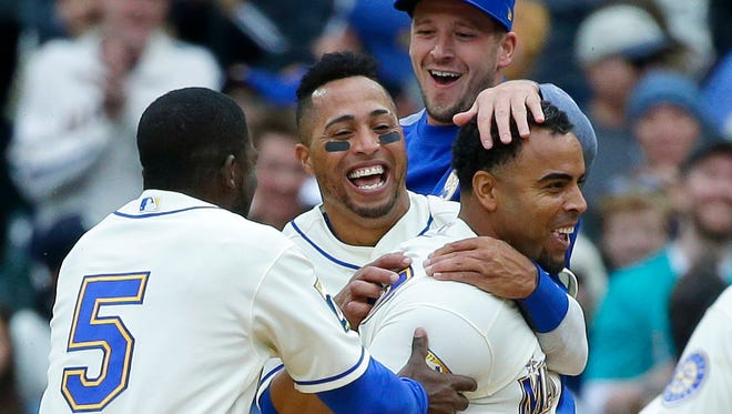 Seattle Mariners' Nelson Cruz (right) is greeted by teammates including Leonys Martin (second from left) and Guillermo Heredia (5) after Cruz hit a walk-off single in the ninth inning to score Mike Freeman and give the Mariners an 8-7 win over the Texas Rangers on Sunday at Safeco Field..