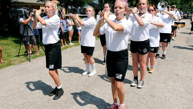 """The Alexandria-Monroe High School marching band performs """"Happy Birthday"""" for Matthew Robinette during a parade for his 21st birthday in front of his Anderson, Ind., home on Saturday, Aug. 19, 2017. (Don Knight/The Herald-Bulletin via AP)"""