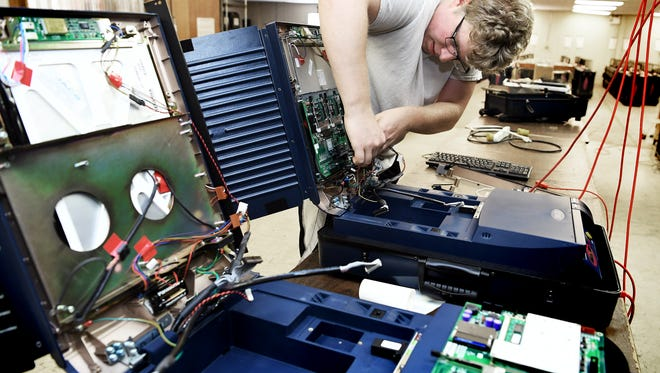 """York County Voting Technology Coordinator Casey Brady removes a circuit board from a non-working voting machine at a storage warehouse in an undisclosed area Thursday, June 7, 2018. He's been in the job for three months. """"It's been a lot to pick up pretty quick,"""" he said. He said the county has 624 working machines and 45 which are in need or repair, or used for parts. In April, Gov. Tom Wolf directed all counties to replace machines, like those used in York County, with new voting machines—all offering paper trails—by 2020.Bill Kalina photo"""