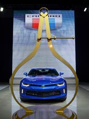 A Chevy Camaro is framed by a Motor Trend award Tuesday, Jan. 12, during the North American International Auto Show at Cobo Hall.