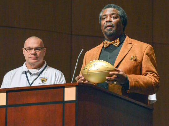 Tony McGee describes to the students and guests in attendance what the significance is of being presented the 50th Super Bowl golden football Friday morning.