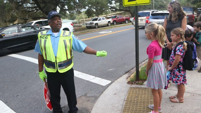 """Crossing Guard Robert Austin, or """"Mr. Bob"""" as he is known to the children, helped students and parents cross the street at Kate Sullivan Elementary School on the first day of classes in 2016."""