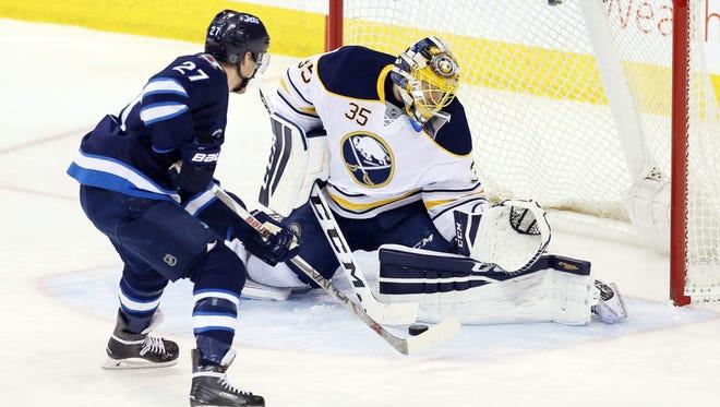Sabres goalie Linus Ullmark makes a save on left winger Nikolaj Ehlers in Sunday's victory over the Winnipeg Jets.