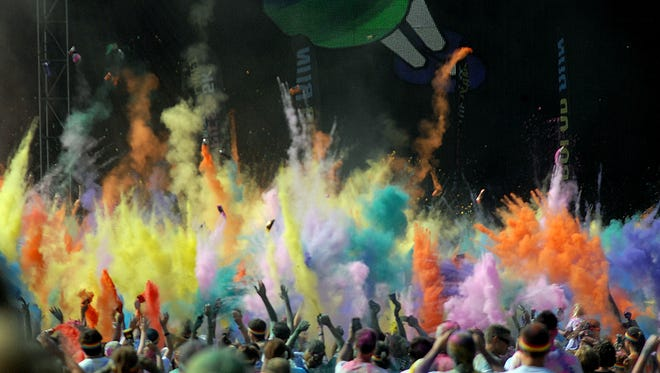 Participants in the Color Run throw dye packets into the air to make a spectacular display Saturday at Adado Riverfront Park in Lansing.