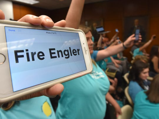 "Sexual assault survivors, family members and supporters hold up cell phones with the words, ""Fire Engler."""