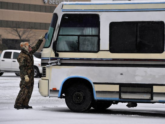 """Bob Krussell, from northern Michigan, scrapes the ice from the windshield of his motor home using a dustpan Wednesday. """"I was on my way up there from here,"""" he said."""