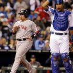 Boston Red Sox's Christian Vazquez crosses the plate past Kansas City Royals catcher Salvador Perez as to score on a two-run double by Jemile Weeks during the eighth inning of a baseball game Thursday, Sept. 11, 2014, in Kansas City, Mo.