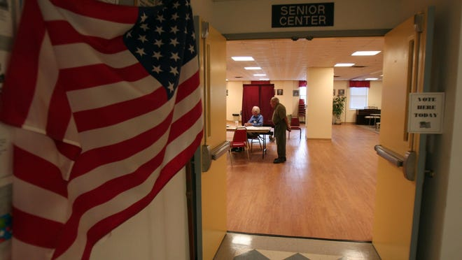 In this June 2012 file photo, election workers Sid Brickel, l, and Wendell Brady of Morristown wait for voters. Results for the 2015 election certified Tuesday showed this year's turnout in New Jersey registered a record low of 22 percent.