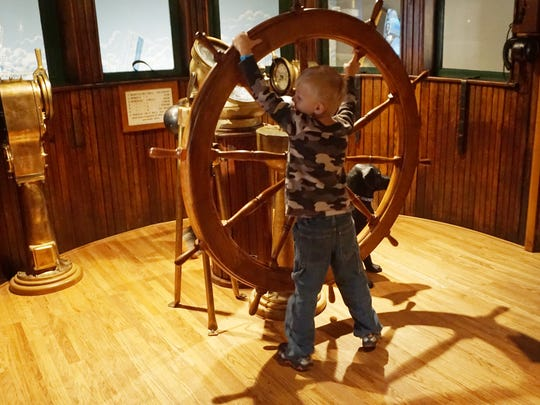 A child visiting the Door County Maritime Museum manipulates the ship's wheel.