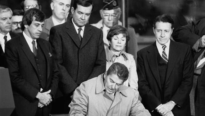 President Ronald Reagan signs the papers accepting the Vietnam Veterans Memorial for the United States government during ceremonies in Washington. With the President are: Jan Scruggs, President of the Memorial Fund, Interior Secretary William Clark and his wife, and Defense Secretary Caspar Weinberger.