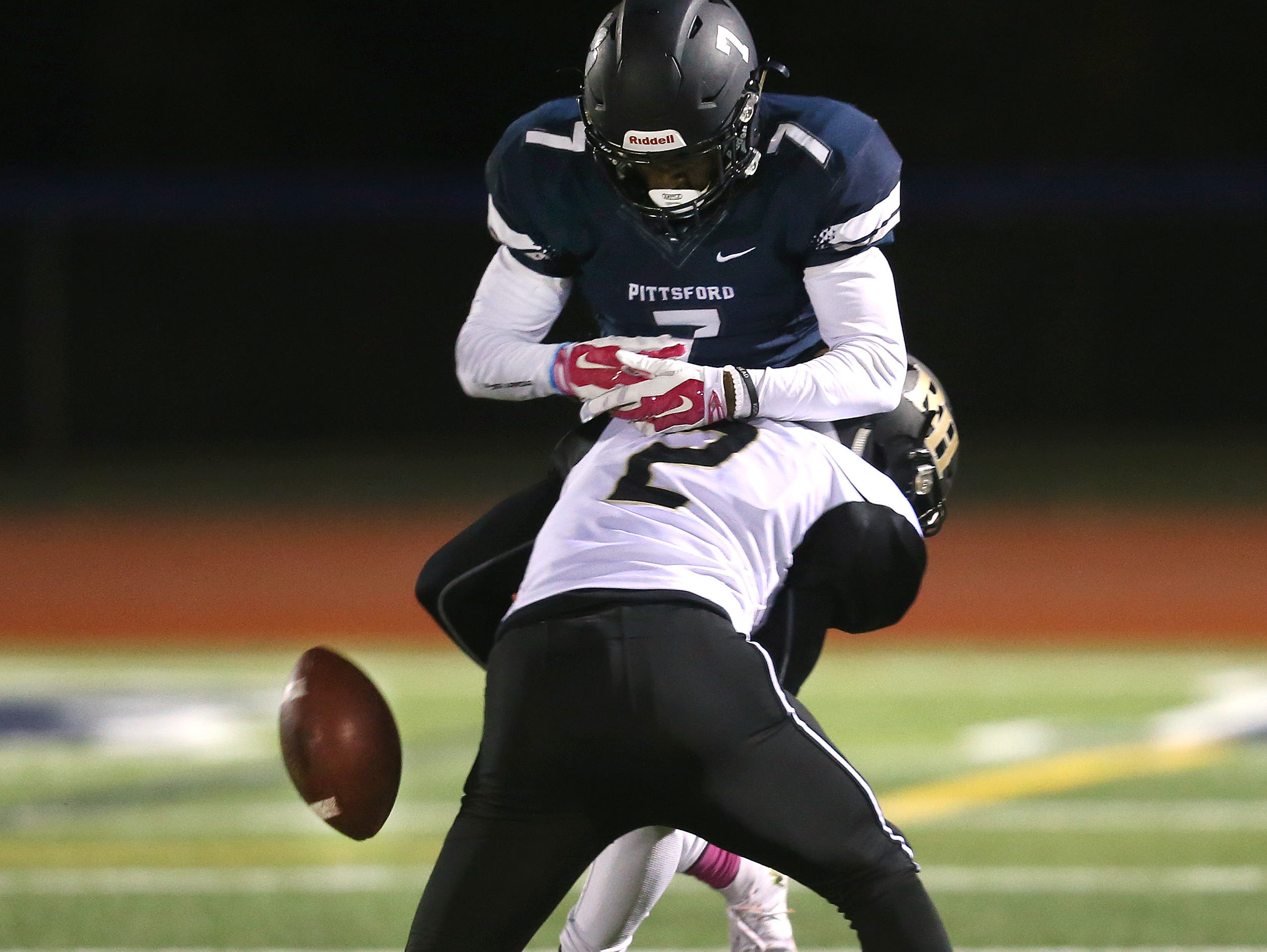 Pittsford's Isaiah Brown (7) has the ball knocked by Rush-Henrietta's Reggie Robinson (2) before securing the catch.