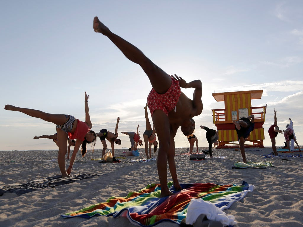 People do yoga at sunrise on the beach in Miami Beach, Fla.