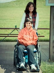 """Lindsey Haynes (in wheelchair) has improved """"greatly"""" after her 2009 accident, her family said. They hope she will get on her feet again."""