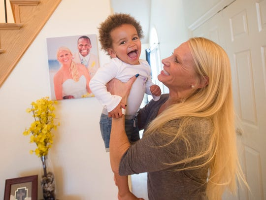 Tracy Whitted, a former college swimmer and coach, and her 20-month-old daughter, Remy, are all smiles Monday at their Fort Collins home.