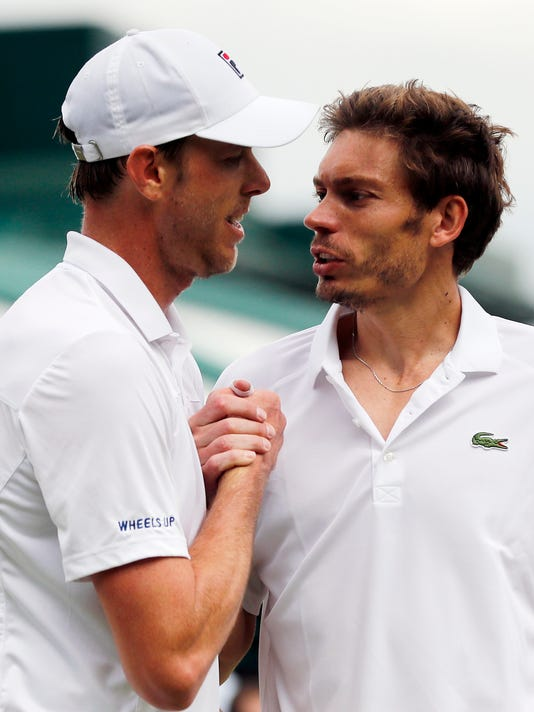 Sam Querrey of the U.S, left, shakes hands with Nicolas Mahut of France after beating him in their men's singles match on day eight of the Wimbledon Tennis Championships in London, Monday, July 4, 2016. (AP Photo/Ben Curtis)
