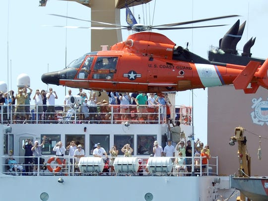 A Coast Guard helicopter makes a low pass alongside the U.S. Coast Guard Cutter Cypress during a Blue Angels Air Show. The cutter is often featured at the Blues' air show at Pensacola Beach.