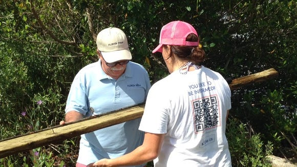 FLORIDA TODAY Fitness & Water reporter Michelle Mulak takes a piece of lumber pulled from the Indian River Lagoon off my hands as we unload the boat of junk Saturday.