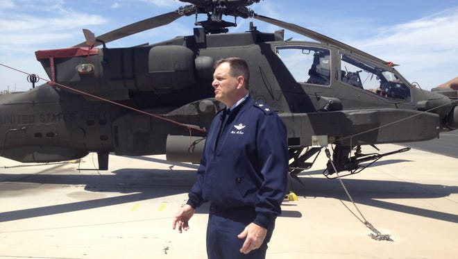 Maj. Gen. Michael McGuire speaks in front of an Apache attack helicopter Friday.