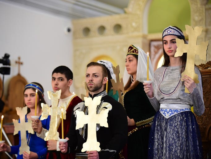 Members of the four area Armenian churches hold candles