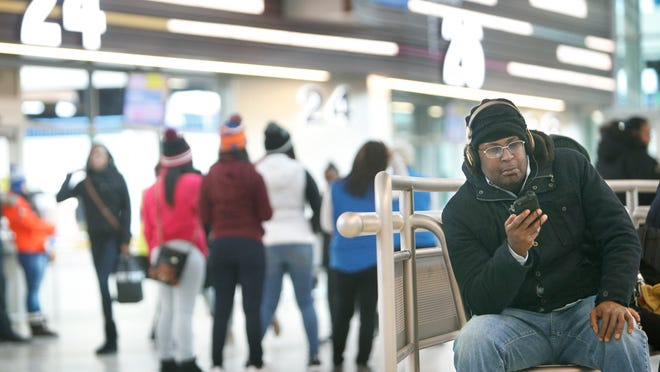 """James Newsom of Rochester listens to music while waiting for the next bus to take him to the west side of town during the Downtown Transit Center's first day Friday. """"Don't have to wait in the cold no more,"""" Newsom said. For Newsom, the bus is his main means of transportation."""
