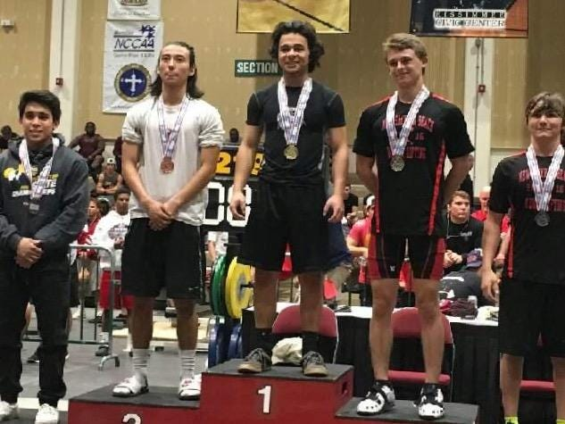 Pace High's Adrian Acevedo stands proudly atop the medal stand after winning the 119-pound weight class at the Class 2A state meet. Acevedo benched 235 pounds and cleaned 225 pounds to finish with a total of 460 pounds.