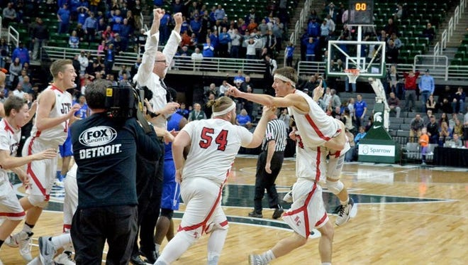 Powers North Central senior Seth Polfus is lifted into the air by a teammate after his lay-up beat the buzzer for an 84-83 win in double overtime over Southfield Christian in a Class D semifinal at the Breslin Center on Thursday, March 23.