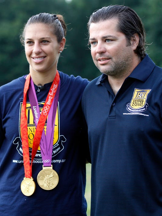 """FILE - In this Aug. 14, 2012, file photo, U.S. women's soccer champ Carli Lloyd wears her gold medals, one from Beijing in 2008 and the other from London 2012, as she visits her coach James Galanis at Universal Soccer Academy in Lumberton, N.J. After being cut from the Under-21 U.S. national team, Lloyd was having a career crisis in 2003. She decided to play out her senior year at Rutgers and """"hang up her boots"""". She then met Galanis, who became her coach and mentor, and helped her become the best women's soccer player in the world. By  (AP Photo/Mel Evans, File)"""