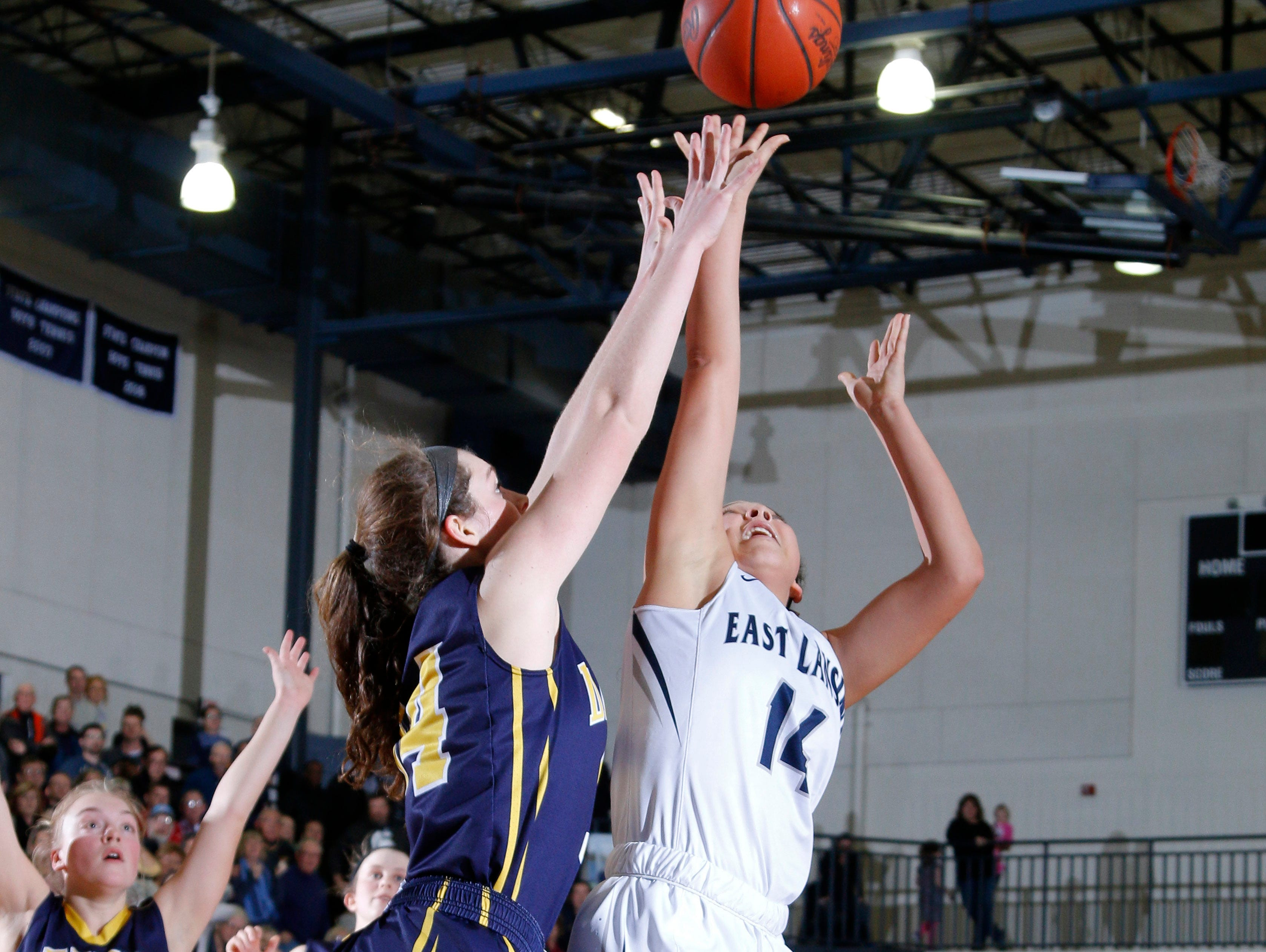 East Lansing's Aazh Nye, right, gets the game-winning shot against DeWitt's Grace George during their district final game Friday, March 3, 2017, in East Lansing, Mich. East Lansing won 48-47.