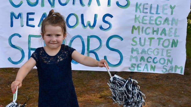 Elementary school student Nora Imbimbo stands in front of a sign a Brentwood resident made of all the seniors in her neighborhood, unveiled this past Friday night in the Brentwood Car Convoy for graduating seniors.