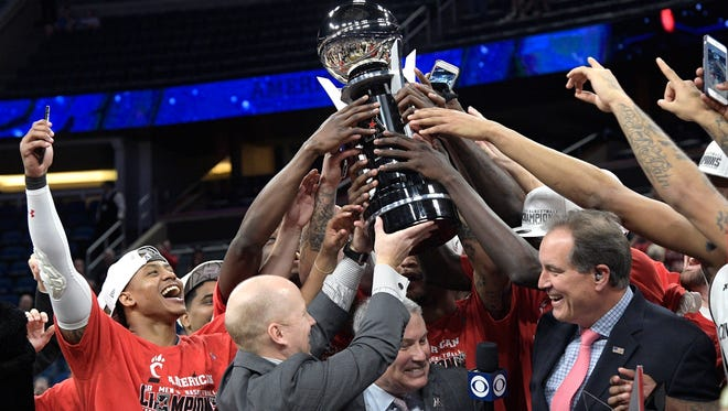 Cincinnati head coach Mick Cronin, second from left, hoists the championship trophy with his players after a win over Houston in an NCAA college basketball championship game at the American Athletic Conference tournament Sunday, March 11, 2018, in Orlando, Fla.