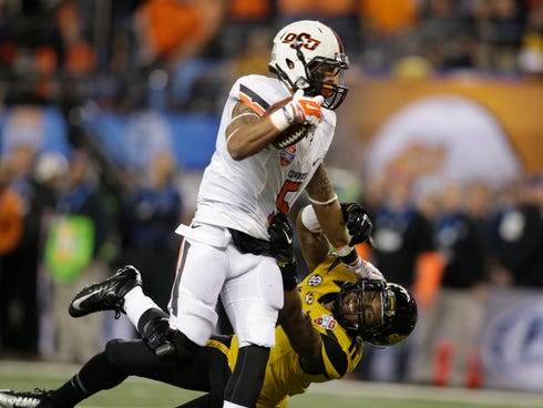Oklahoma State wide receiver Josh Stewart  stiff arms Missouri defensive back Aarion Penton on the way to a touchdown.