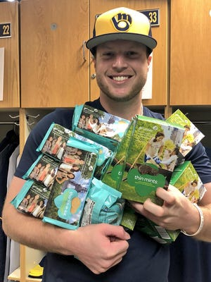 From his locker in Arizona ahead of spring training, Milwaukee Brewers outfielder Brett Phillips shows off his Thanks-A-Lot and Thin Mints Girl Scout cookies he bought from Oconomowoc's Claire Henke. Henke sold to many Brewers players after her dad sent a video to the team with her request.