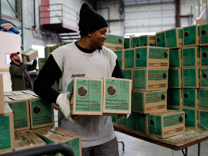 Rick Moon stacks cases of Girl Scout Cookies to be loaded into the cars of Girl Scout troop leaders and volunteers as they pick up their cookie orders at Berger Allied Warehouse. Karen Smallwood, the Girl Scouts of Kentuckiana product sales manager, estimates that 147,000 cases, which totals 1.4 million boxes of cookies, will be picked up by troops over four days.   Feb. 16, 2014