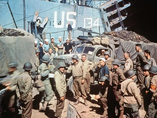 UTAH BEACH, FRANCE:  US soldiers gather around trucks disembarking from landing crafts shortly after D-Day 06 June 1944 after Allied forces stormed the Normandy beaches. D-Day, 06 June 1944 is still one of the world's most gut-wrenching and consequential battles, as the Allied landing in Normandy led to the liberation of France which marked the turning point in the Western theater of World War II.