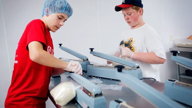 Ben Sheorn, left, and Will Schaible seal bags of rice at MANNA Food Bank June 27.