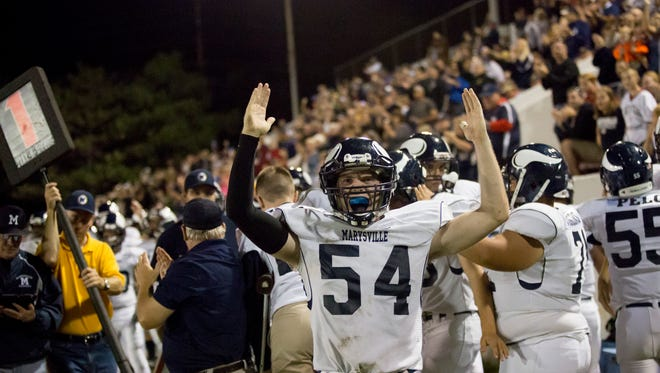 Marysville players celebrate on the sidelines during a football game.