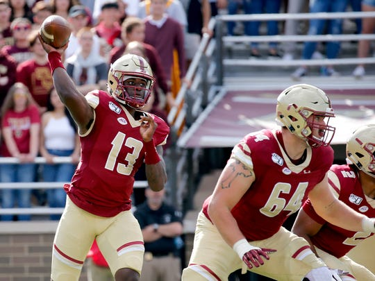 Boston College QB Anthony Brown (13) looks to pass as Ben Petrula (64) and AJ Dillon (2) block during a game this season.