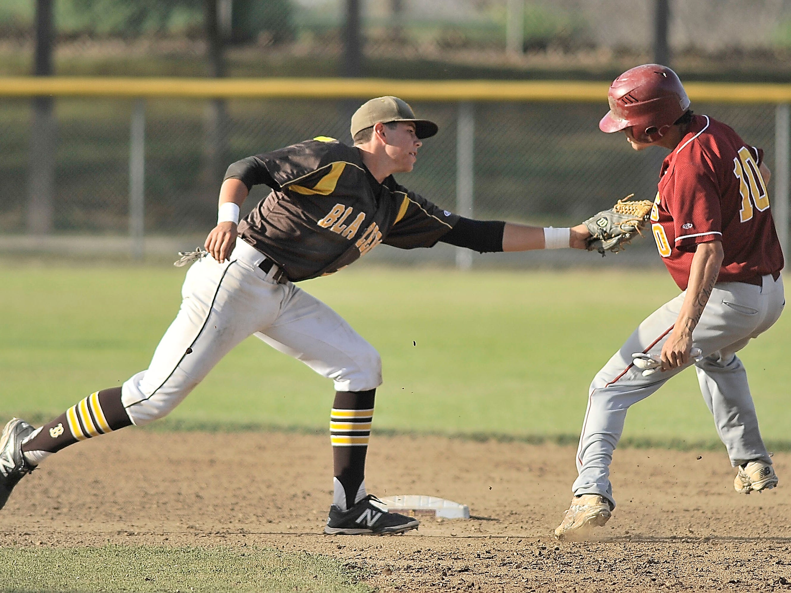 Golden West's Wyatt Tilley, left, tries to apply the tag to Tulare Union's Jonathan Pinheiro during a Tulare/Visalia Invitational game Tuesday.