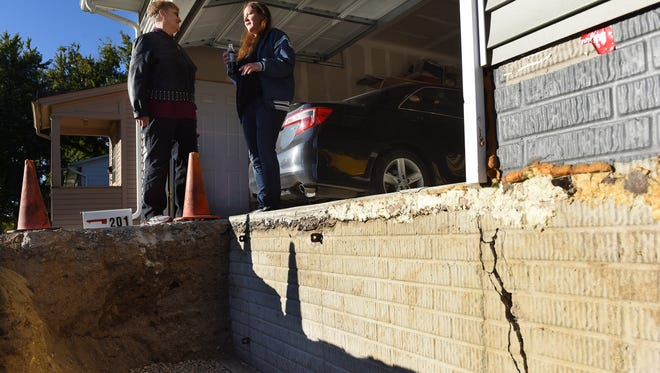 Erika Leacraft and neighbor Gail Grace (left) talk about cracks in their foundation like the one seen in this pic at right at Leacraft's home in central Sioux Falls recently.