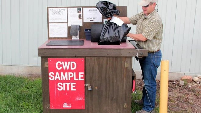 Tim Lizotte, a wildlife supervisor for the Wisconsin Department of Natural Resources, checks a kiosk last September at Kettle Moraine State Forest in Eagle that allows hunters to deposit deer samples for aging and chronic wasting disease testing.