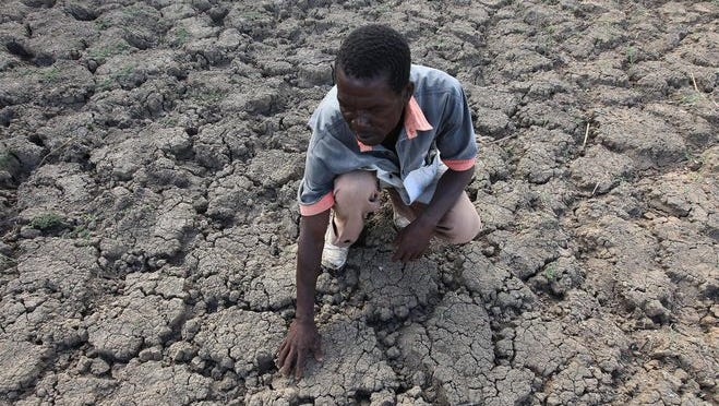 Last Zimaniwa feels the broken ground at a spot which is usually a reliable water source that has dried up due to lack of rains in the village of Chivi , Zimbabwe, in January 2016.