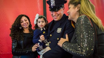 Matias Ferreira, center, celebrates with his 2-year-old daughter, his wife, left, and his mother during his graduation from the Suffolk County Police Department Academy at the Health, Sports and Education Center in Suffolk, Long Island, New York, on Friday.